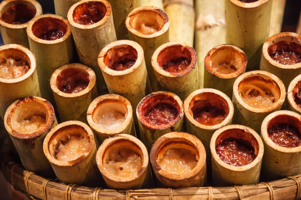 Khao Lam, Traditional Thai Asian sweet custard sticky rice dessert snack made with boiled sticky rice, red bean, sugar, grated coconut and coconut milk roasted in bamboo tube. Thai Food Travel concept
